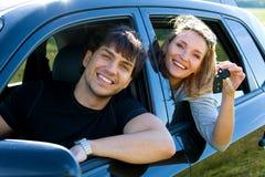Lyckliga par i ny bil fotografering för bildbyråer