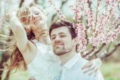 Lyckliga par i parkera med äppleträdet blomstrar Det lyckliga ung flickainnehav hänger lös på en vitbakgrund Arkivfoton