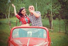 Lyckliga par i retro röd bil Fotografering för Bildbyråer