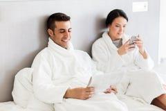 Lyckliga par i säng hemma eller hotellrum Arkivbilder