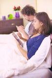 Lyckliga par i säng som har gyckel med retro stil för mobiltelefon och för minnestavla Royaltyfri Bild
