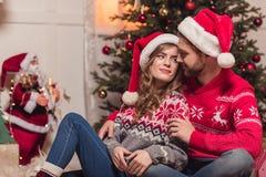Lyckliga par i santa hattar Royaltyfria Bilder