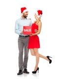 Lyckliga par i santa hattar med röd försäljning undertecknar Royaltyfri Fotografi