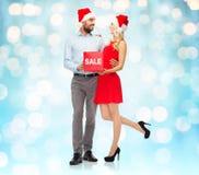 Lyckliga par i santa hattar med röd försäljning undertecknar Fotografering för Bildbyråer