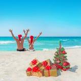 Lyckliga par i santa hattar på havet sätter på land nära julträd royaltyfria foton