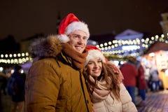 Lyckliga par i santa hattar på jul marknadsför Royaltyfria Foton