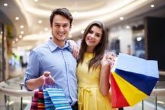 Lyckliga par i shoppinggalleria Royaltyfria Foton