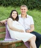 Lyckliga par i sommarstad parkerar utomhus-, gravida kvinnan, den ljusa soliga dagen och grönt gräs, den härliga folkståenden, gu Arkivbild