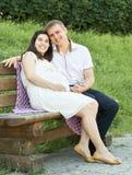 Lyckliga par i sommarstad parkerar utomhus-, gravida kvinnan, den ljusa soliga dagen och grönt gräs, den härliga folkståenden, gu Royaltyfri Foto