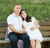 Lyckliga par i sommarstad parkerar utomhus-, gravida kvinnan, den ljusa soliga dagen och grönt gräs, den härliga folkståenden, gu Arkivfoto