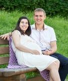 Lyckliga par i sommarstad parkerar utomhus-, gravida kvinnan, den ljusa soliga dagen och grönt gräs, härlig folkstående Fotografering för Bildbyråer