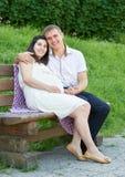 Lyckliga par i sommarstad parkerar utomhus-, gravida kvinnan, den ljusa soliga dagen och grönt gräs, härlig folkstående Arkivbild