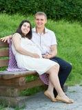 Lyckliga par i sommarstad parkerar utomhus-, gravida kvinnan, den ljusa soliga dagen och grönt gräs, härlig folkstående Royaltyfria Foton