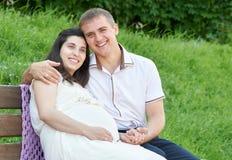 Lyckliga par i sommarstad parkerar utomhus-, gravida kvinnan, den ljusa soliga dagen och grönt gräs, härlig folkstående Royaltyfri Bild