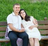 Lyckliga par i sommarstad parkerar utomhus-, gravida kvinnan, den ljusa soliga dagen och grönt gräs, härlig folkstående Royaltyfri Foto