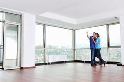 Lyckliga par i tom lägenhet royaltyfri bild