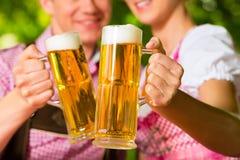 Lyckliga par i trädgårds- dricka öl för öl Royaltyfri Bild