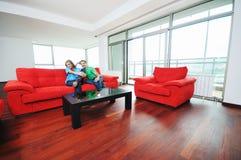 Lyckliga par kopplar av på den röda sofaen arkivbild
