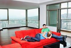 Lyckliga par kopplar av på den röda sofaen royaltyfria foton