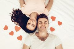 Lyckliga par ligger i säng på dagen för valentin` s arkivbilder
