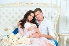 Lyckliga par: maken och den gravida frun som väntar på, behandla som ett barn Arkivfoto