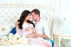 Lyckliga par: maken och den gravida frun som väntar på, behandla som ett barn Arkivfoton