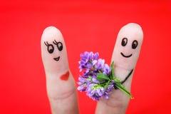 lyckliga par Mannen ger blommor till en kvinna Arkivfoto