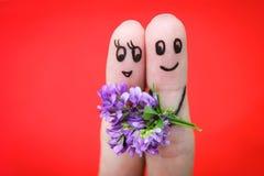 lyckliga par Mannen ger blommor till en kvinna Royaltyfria Bilder
