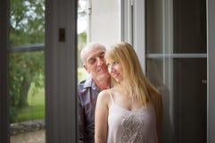 Lyckliga par med ålderskillnaden som omfamnar stående near öppnade Windows i rummet under sommar Tid Psykologi av Arkivbild