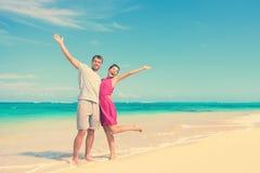 Lyckliga par med armar lyftt anseende på stranden Royaltyfria Bilder