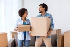Lyckliga par med askar som flyttar sig till det nya hemmet Arkivfoton