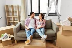 Lyckliga par med askar som flyttar sig till det nya hemmet royaltyfri bild