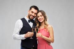 Lyckliga par med att rosta för champagneexponeringsglas arkivfoton