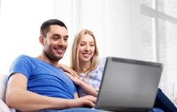 Lyckliga par med bärbar datordatoren hemma fotografering för bildbyråer
