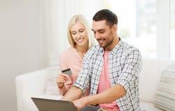 Lyckliga par med bärbara datorn och kreditkorten hemma Arkivfoton
