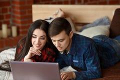 Lyckliga par med bärbara datorn som direktanslutet hemma shoppar, bläddrar internet i säng, ler och har gyckel Royaltyfria Foton