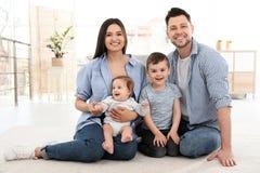 Lyckliga par med barn som sitter på golv helg f?r fader f?r cykelbarnfamilj royaltyfri bild