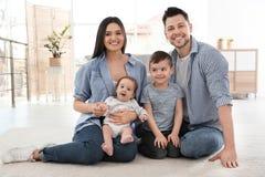 Lyckliga par med barn som sitter p? golv helg f?r fader f?r cykelbarnfamilj arkivfoto