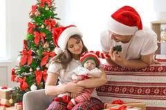 Lyckliga par med behandla som ett barn i julhattar Royaltyfria Bilder