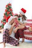 Lyckliga par med behandla som ett barn i julhattar Fotografering för Bildbyråer