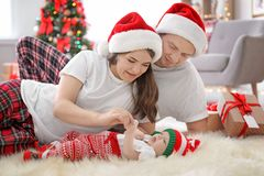Lyckliga par med behandla som ett barn i julhattar Arkivfoto
