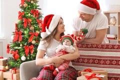 Lyckliga par med behandla som ett barn i julhattar Royaltyfri Foto