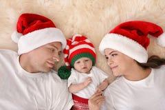 Lyckliga par med behandla som ett barn i julhattar på den luddiga filten Royaltyfri Foto