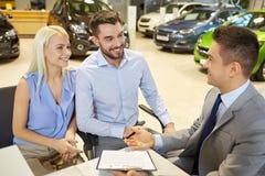 Lyckliga par med bilåterförsäljaren i auto show eller salong Royaltyfria Bilder