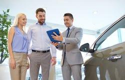 Lyckliga par med bilåterförsäljaren i auto show eller salong Arkivbilder