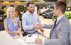 Lyckliga par med bilåterförsäljaren i auto show eller salong Royaltyfri Foto