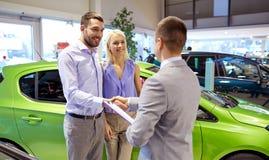 Lyckliga par med bilåterförsäljaren i auto show eller salong Arkivfoton