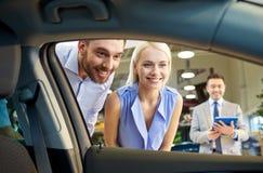 Lyckliga par med bilåterförsäljaren i auto show eller salong Royaltyfria Foton