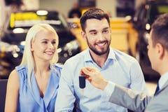 Lyckliga par med bilåterförsäljaren i auto show eller salong Arkivbild