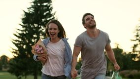 Lyckliga par med blommor som kör i sommar, parkerar förbunden förälskelse lager videofilmer
